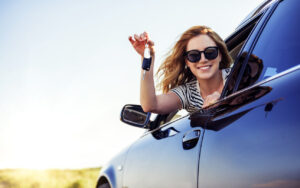 An attractive woman in a car holds a car key in her hand.