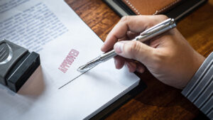Close up hands of businessman signing and stamp on paper document to approve business investment contract agreement
